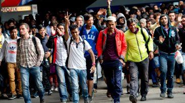 Flüchtlinge, die kurz zuvor mit einem Zug angekommen sind, jubeln am 06.09.2015 auf dem Hauptbahnhof in München (Bayern) auf einem Bahnsteig. Foto: Sven Hoppe/dpa +++(c) dpa - Bildfunk+++