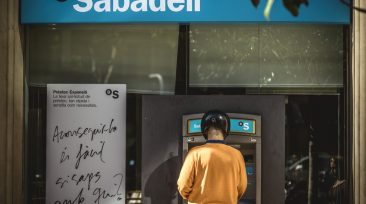 A customer stands at an ATM of the 'Banco Sabadell', the fifth-largest banking group in Spain, the day on which it will announce the relocation of its headquarters from Catalonia to Alicante in the Valencian Community, in Barcelona, Spain, 05 October 2017. The Catalan regional government said it is on the move to declare independence on 09 October 2017. Photo: Matthias Oesterle/ZUMA Wire/dpa